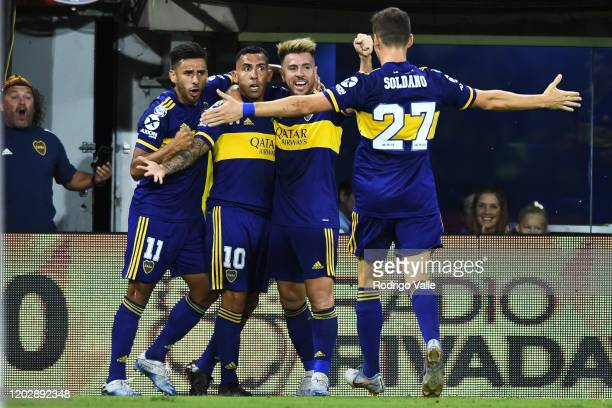 Carlos Tevez of Boca Juniors celebrates with teammates Julio Buffarini and Eduardo Salvio after scoring the first goal of his team during a match...