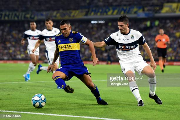 Carlos Tevez of Boca Juniors drives the ball against Maximiliano Coronel of Gimnasia during a match between Boca Juniors and Gimnasia as part of...