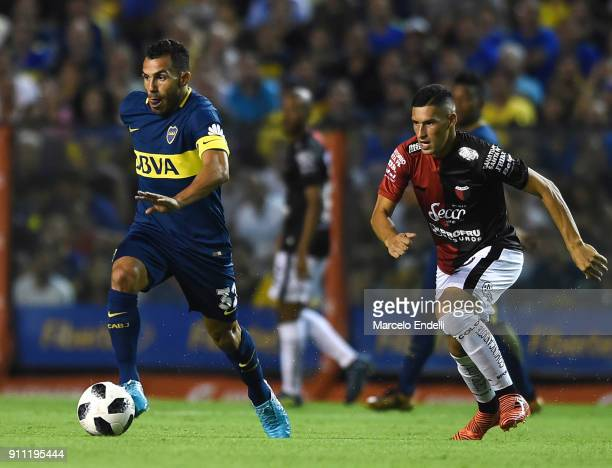 Carlos Tevez of Boca Juniors drives the ball followed by Cristian Guanca of Colon during a match between Boca Juniors and Colon as part of the...