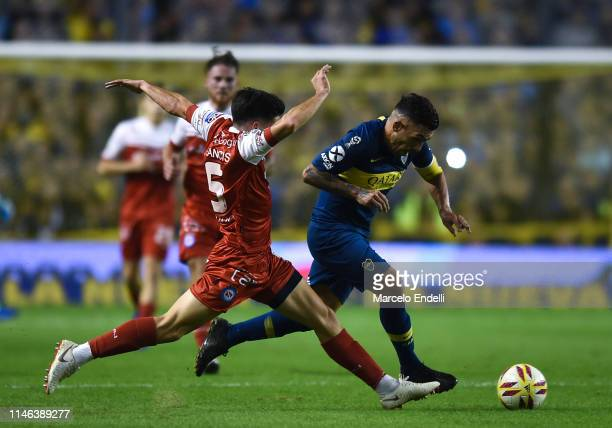 Carlos Tevez of Boca Juniors fights for the ball with Francis Mac Allister of Argentinos Juniors during a second leg semifinal match between Boca...