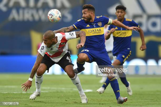 Carlos Tevez of Boca Juniors fights for the ball with Jonathan Maidana of River Plate during a match between Boca Juniors and River Plate as part of...