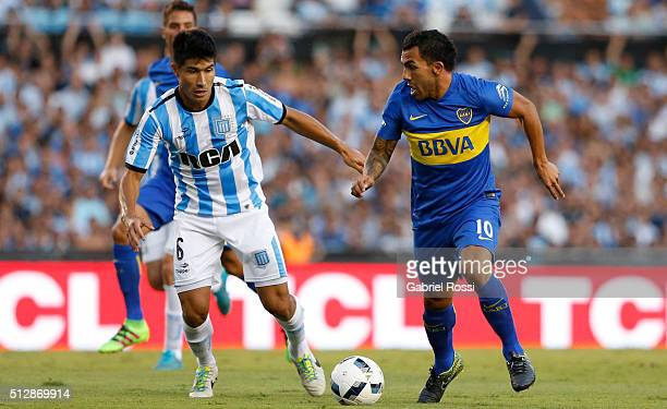 Carlos Tevez of Boca Juniors fights for the ball with Luciano Lollo of Racing Club during a fifth round match between Racing Club and Boca Juniors as...