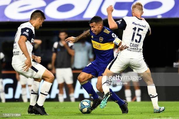 Carlos Tevez of Boca Juniors fights for the ball with Maximiliano Caire and Paolo Goltz of Gimnasia during a match between Boca Juniors and Gimnasia...