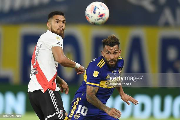 Carlos Tevez of Boca Juniors fights for the ball with Paulo Díaz of River Plate during a match between Boca Juniors and River Plate as part of Copa...