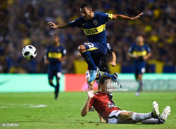Carlos Tevez of Boca Juniors jumps over German Conti of Colon during a match between Boca Juniors and Colon as part of the Superliga 2017/18 at...