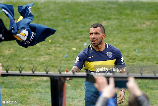 Carlos Tevez of Boca Juniors receives a shirt from fans during Boca Juniors team presentation at Alberto J Armando Stadium on August 19 2016 in...