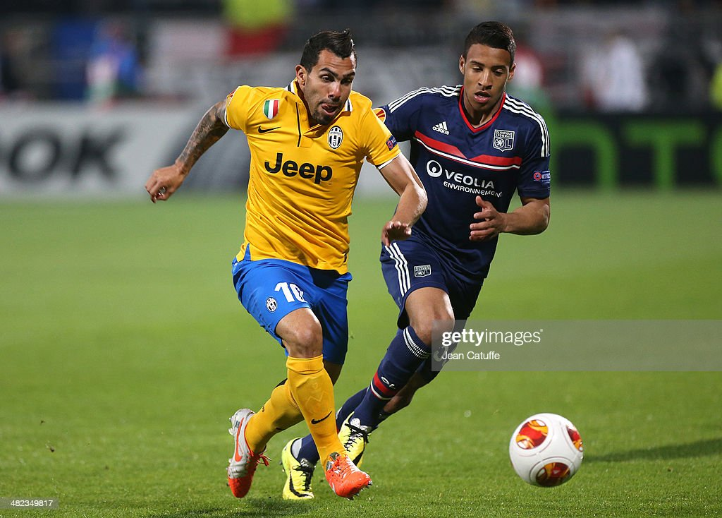 Carlos Tevez of Juventus and Corentin Tolisso of Lyon in action during the UEFA Europa League quarter final match between Olympique Lyonnais OL and Juventus at Stade de Gerland on April 3, 2014 in Lyon, France.
