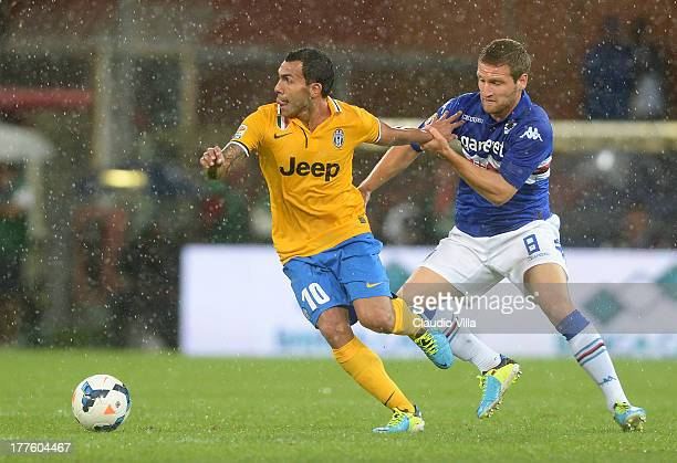 Carlos Tevez of Juventus and Shkodran Mustafi of UC Sampdoria compete for the ball during the Serie A match between UC Sampdoria and Juventus at...