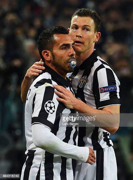 Carlos Tevez of Juventus celebrates with Stephan Lichtsteiner as he score their first goal during the UEFA Champions League Round of 16 first leg...