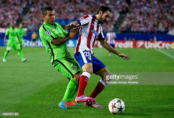 Carlos Tevez of Juventus competes for the ball with Juan Francisco Torres alias Juanfran of Atletico de Madrid during the UEFA Champions League group...