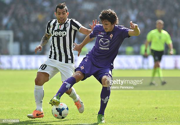 Carlos Tevez of Juventus competes with Stefan Savic of ACF Fiorentina during the Serie A match between Juventus and ACF Fiorentina at Juventus Arena...