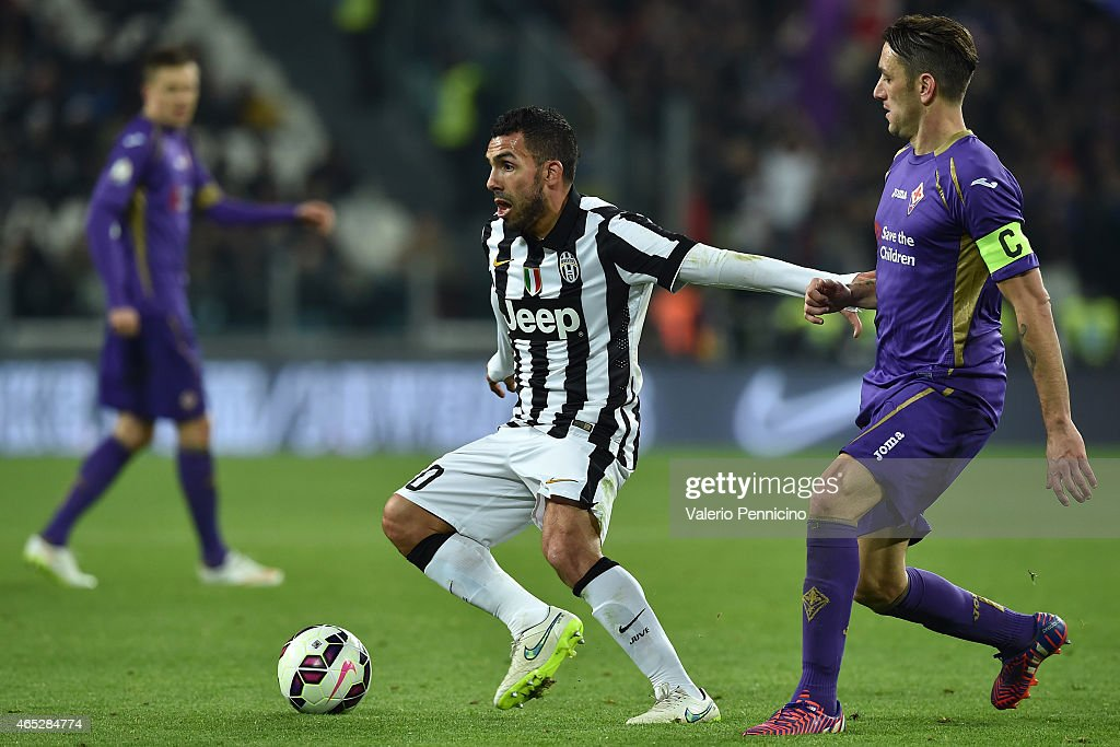 Carlos Tevez (L) of Juventus FC is challenged by Gonzalo Rodriguez of ACF Fiorentina during the TIM Cup match between Juventus FC and ACF Fiorentina at Juventus Arena on March 5, 2015 in Turin, Italy.