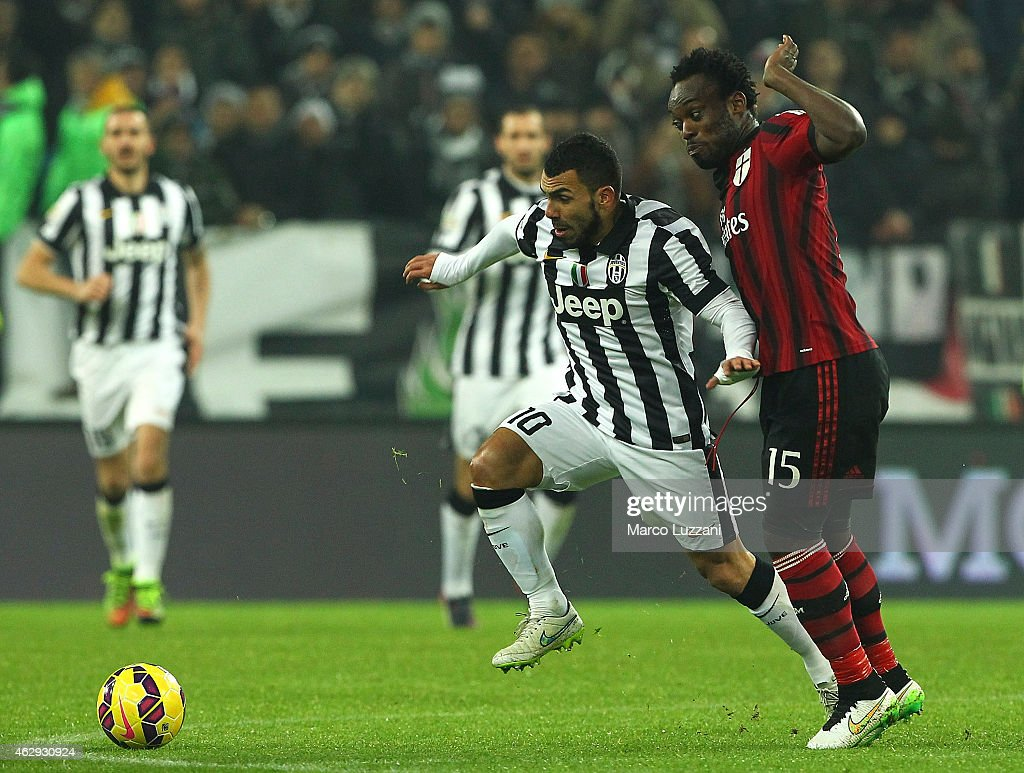 Carlos Tevez of Juventus FC is challenged by Michael Essien of AC Milan during the Serie A match between Juventus FC and AC Milan at Juventus Arena on February 7, 2015 in Turin, Italy.