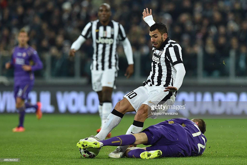 Carlos Tevez (L) of Juventus FC is tackled by Josip Ilicic of ACF Fiorentina during the TIM Cup match between Juventus FC and ACF Fiorentina at Juventus Arena on March 5, 2015 in Turin, Italy.
