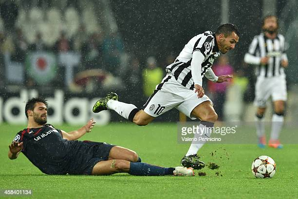 Carlos Tevez of Juventus is tackled by Alberto Botia of Olympiacos FC during the UEFA Champions League group A match between Juventus and Olympiacos...