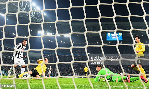 Carlos Tevez of Juventus scores their second goal past a grounded goalkeeper Roman Weidenfeller of Borussia Dortmund during the UEFA Champions League...