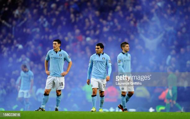 Carlos Tevez of Manchester City and teammate Gareth Barry look dejected after conceding a third goal during the Barclays Premier League match between...