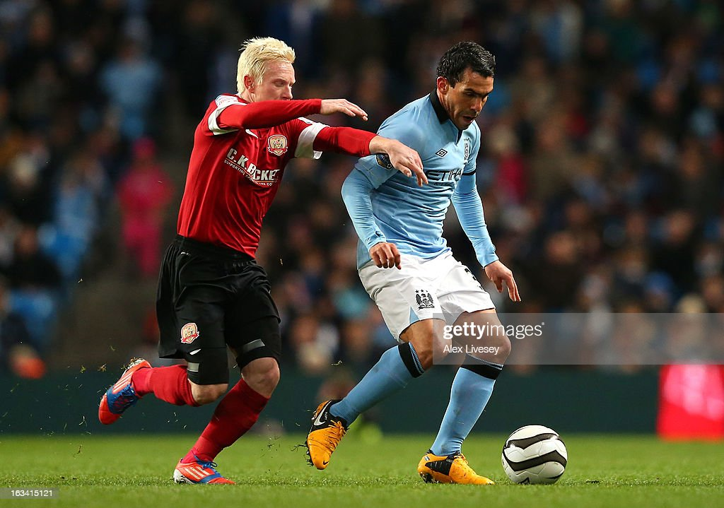 Carlos Tevez of Manchester City beats David Perkins of Barnsley during the FA Cup sponsored by Budweiser sixth round match between Manchester City and Barnsley at Etihad Stadium on March 9, 2013 in Manchester, England.