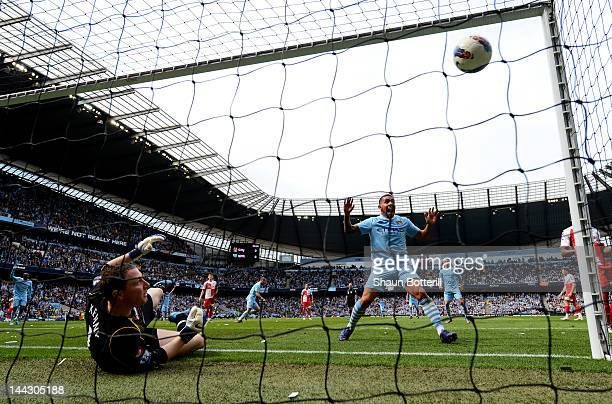 Carlos Tevez of Manchester City celebrates as the shot from teammate Pablo Zabaleta beats goalkeeper Paddy Kenny of QPR for the opening goal during...