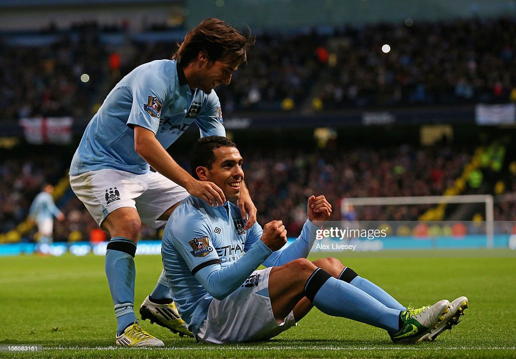 Carlos Tevez of Manchester City celebrates scoring his team's third goal, from the penalty spot, to make the score 3-0 with team-mate David Silva (L) during the Barclays Premier League match between Manchester City and Aston Villa at the Etihad Stadium on November 17, 2012 in Manchester, England.
