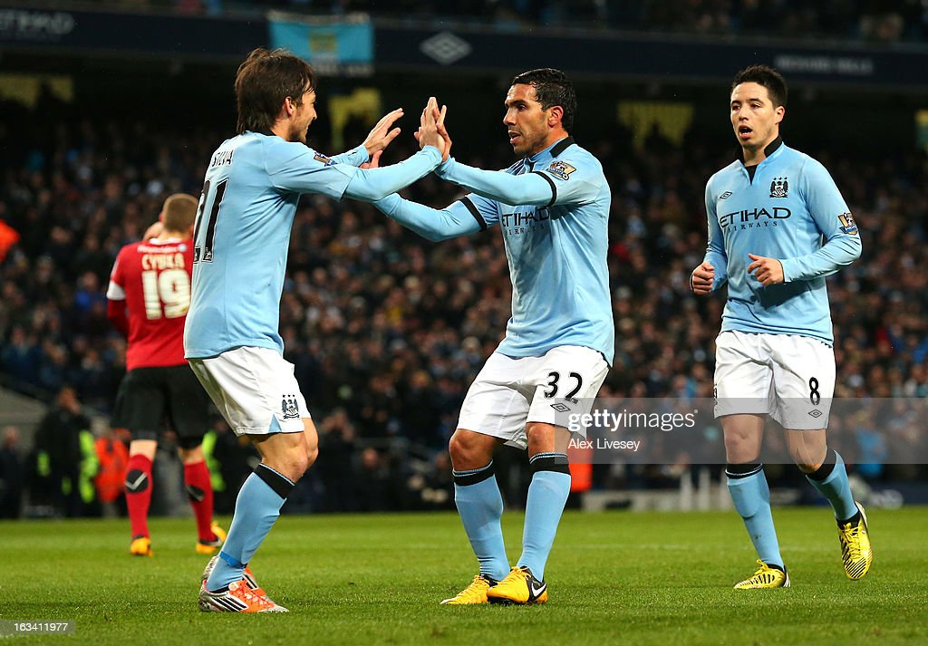 Carlos Tevez of Manchester City celebrates with David Silva after scoring the third goal during the FA Cup sponsored by Budweiser sixth round match between Manchester City and Barnsley at Etihad Stadium on March 9, 2013 in Manchester, England.