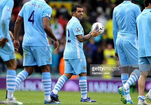 Carlos Tevez of Manchester City claims the match ball after completing a hat trick during the Barclays Premier League match between Norwich City and...