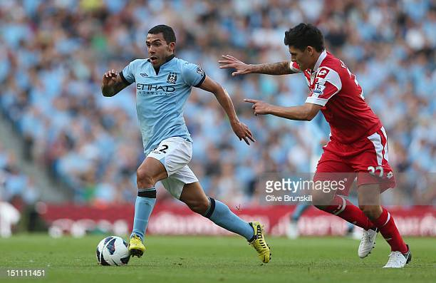 Carlos Tevez of Manchester City moves away from Alejandro Faurlin of Queens Park Rangers during the Barclays Premier League match between Manchester...