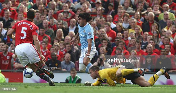 Carlos Tevez of Manchester City rounds Ben Foster of Manchester United in the build-up to Gareth Barry scoring their first goal during the Barclays...