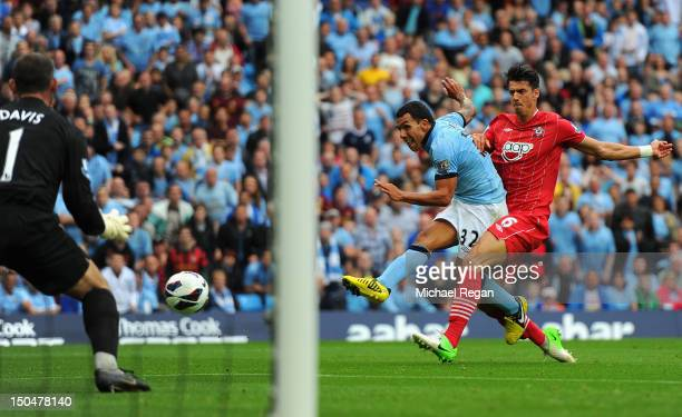 Carlos Tevez of Manchester City scores the opening goal during the Barclays Premier League match between Manchester City and Southampton at Etihad...