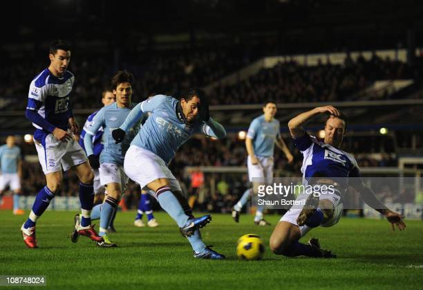 Carlos Tevez of Manchester City shoots past Martin Jiranek of Birmingham City to score during the Barclays Premier League match between Birmingham...