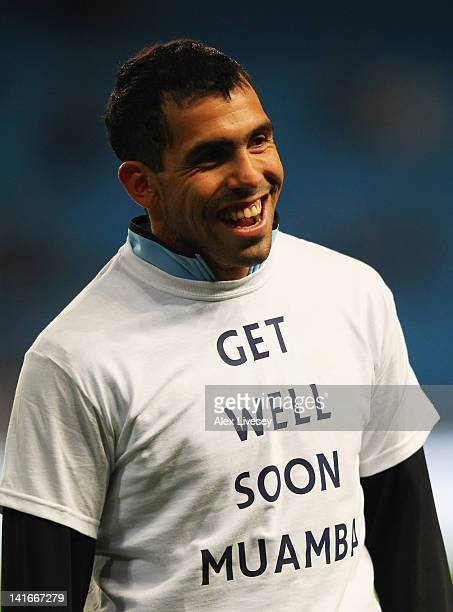 Carlos Tevez of Manchester City wears a tshirt in support of Fabrice Muamba as he warms up prior to during the Barclays Premier League match between...