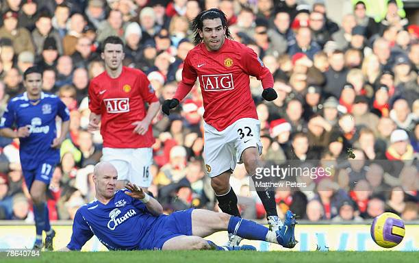 Carlos Tevez of Manchester United clashes with Andy Johnson of Everton during the Barclays FA Premier League match between Manchester United and...