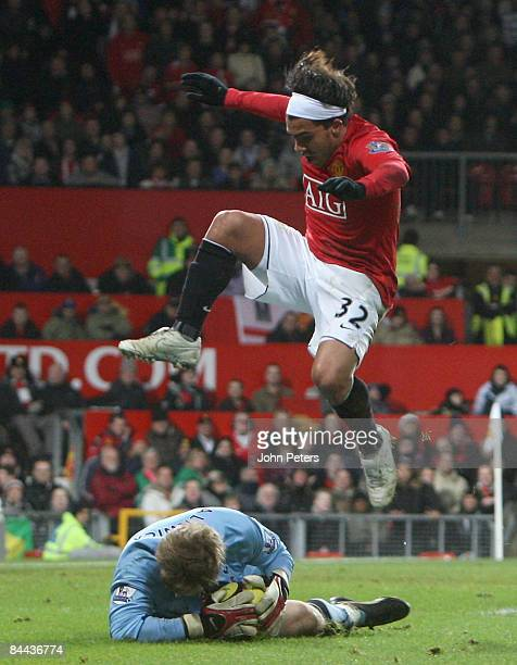 Carlos Tevez of Manchester United clashes with Ben Alnwick of Tottenham Hotspur during the FA Cup sponsored by eon Fourth Round match between...