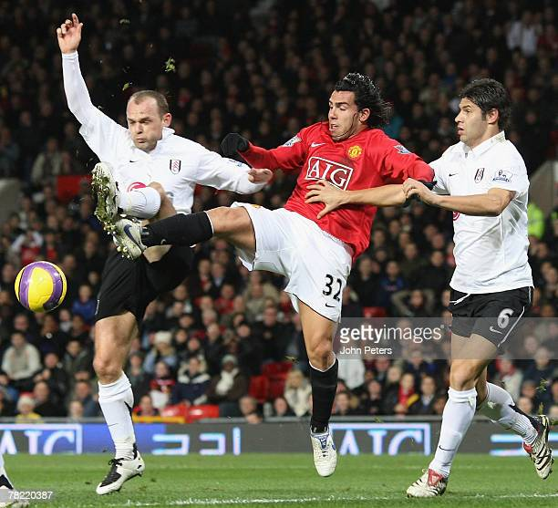 Carlos Tevez of Manchester United clashes with Danny Murphy and Dejan Stefanovic of Fulham during the Barclays FA Premier League match between...