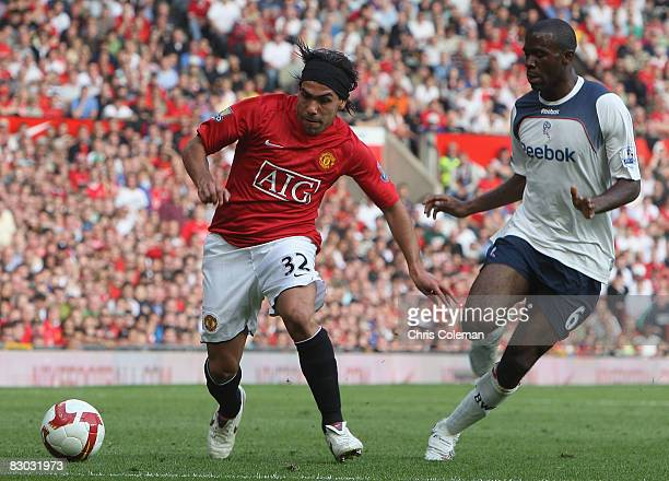 Carlos Tevez of Manchester United clashes with Fabrice Muamba of Bolton Wanderers during the FA Premier League match between Manchester United and...