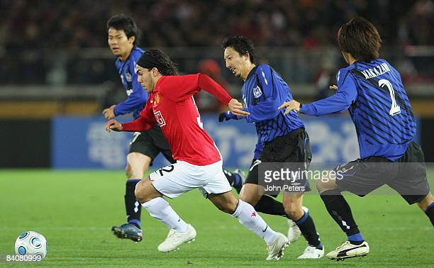 Carlos Tevez of Manchester United clashes with Hideo Hashimoto of Gamba Osaka during the FIFA World Club Cup Semi-Final match between Gamba Osaka and...