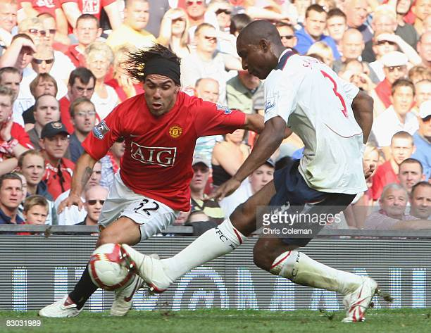 Carlos Tevez of Manchester United clashes with Jlloyd Samuel of Bolton Wanderers during the FA Premier League match between Manchester United and...