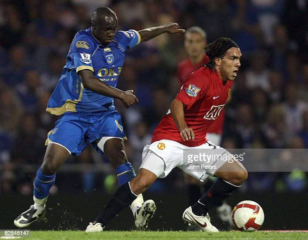Carlos Tevez of Manchester United clashes with Lassana Diarra of Portsmouth during the FA Premier League match between Portsmouth and Manchester...