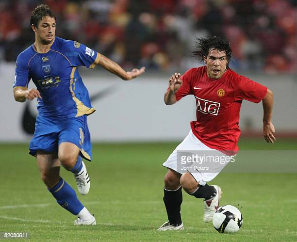 Carlos Tevez of Manchester United clashes with Niko Kranjcar during the preseason friendly match between Manchester United and Portsmouth during...