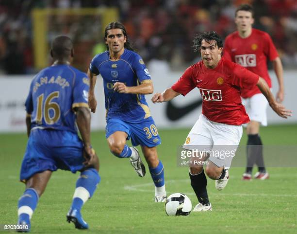 Carlos Tevez of Manchester United clashes with Noe Pamarot during the preseason friendly match between Manchester United and Portsmouth during their...