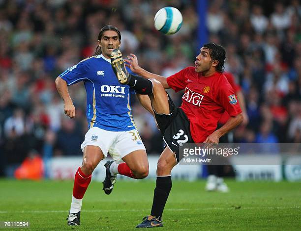 Carlos Tevez of Manchester United controls the ball as Pedro Mendes of Portsmouth closes during the Barclays Premier League match between Portsmouth...