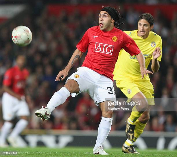 Carlos Tevez of Manchester United is challenged by Edmilson of Villarreal during the UEFA Champions League match between Manchester United and...