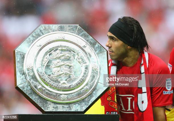 Carlos Tevez of Manchester United stands with the trophy as they are victorious on penalty kicks during the FA Community Shield match between...