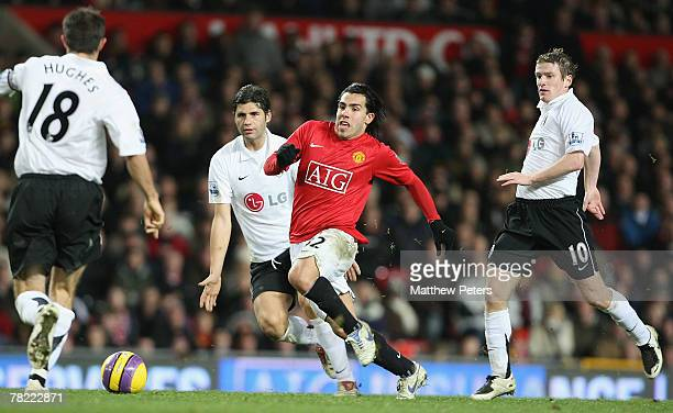 Carlos Tevez of Manchester Unted clashes with Aaron Hughes and Dejan Stefanovic of Fulham during the Barclays FA Premier League match between...