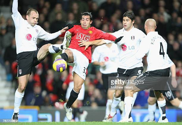 Carlos Tevez of Manchester Unted clashes with Danny Murphy and Dejan Stefanovic of Fulham during the Barclays FA Premier League match between...