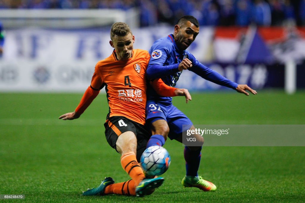 Carlos Tevez #32 of Shanghai Shenhua and Daniel Bowles #4 of Brisbane Roar compete for the ball during the AFC Champions League 2017 play-off match between Shanghai Shenhua and Brisbane Roar at Hongkou Stadium on February 8, 2017 in Shanghai, China.