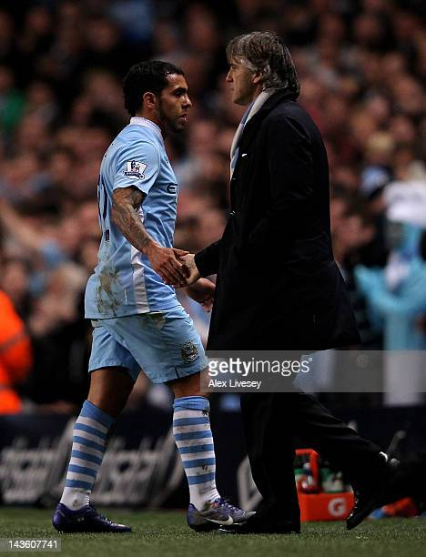 Carlos Tevez shakes hands with Manchester City Manager Roberto Mancini as he is substituted during the Barclays Premier League match between...