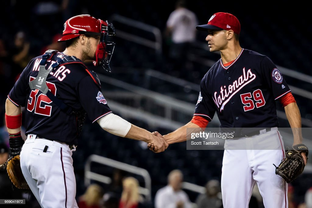 Carlos Torres #59 and Matt Wieters #32 of the Washington Nationals celebrate after the game against the Pittsburgh Pirates at Nationals Park on May 1, 2018 in Washington, DC. Nationals won 12-4.