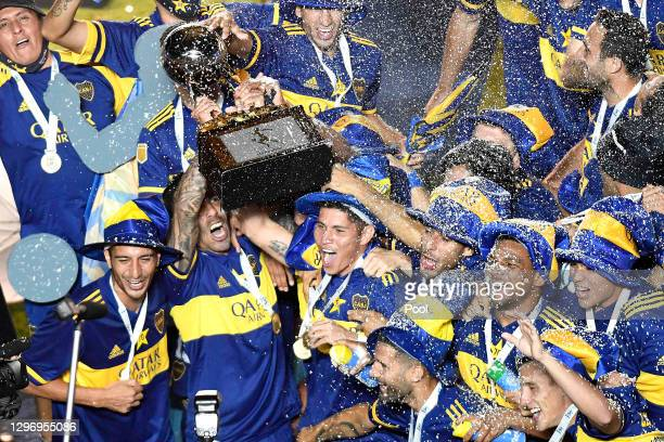 Carlos Tévez of Boca Juniors lifts the trophy to celebrate with teammates after winning the final match between Banfield and Boca Juniors as part of...