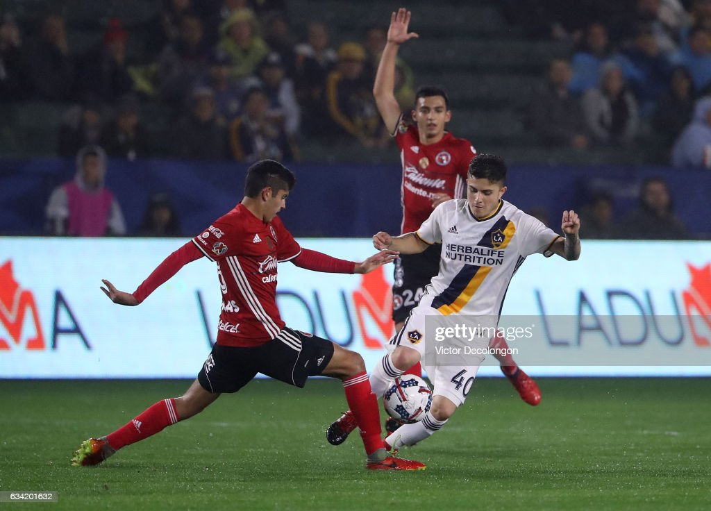 Carlos Vargas #88 of Club Tijuana and Raul Mendola #40 of the Los Angeles Galaxy vie for the ball at midfield during the first half of their friendly match at StubHub Center on February 7, 2017 in Carson, California.